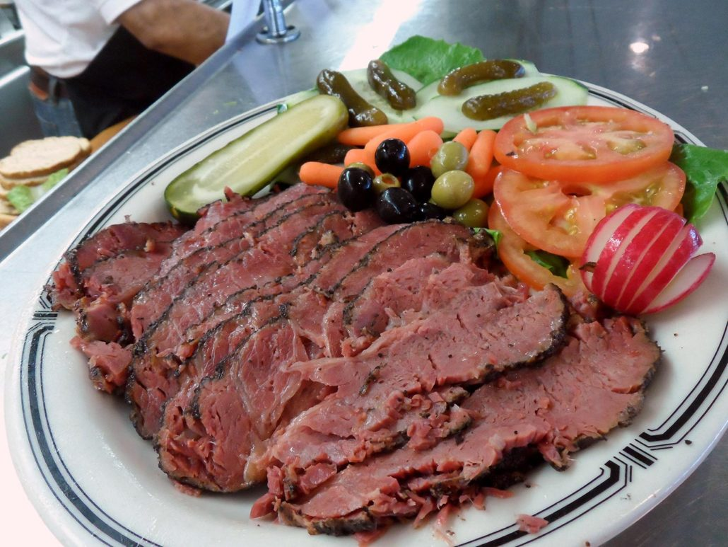 plate full of hot, sliced pastrami with a pickle, olives, tomatoes and other garnishes