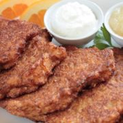 Langer's latkes on a plate with side dishes