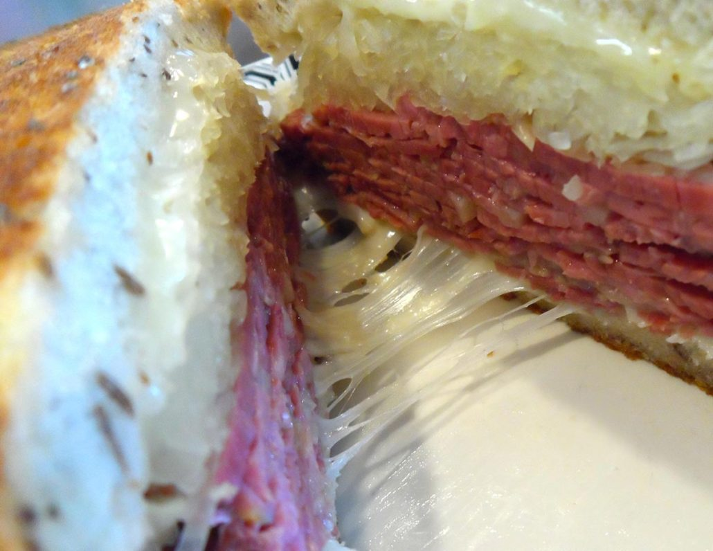close up of a rueben sandwich with strings of cheese between the 2 halves