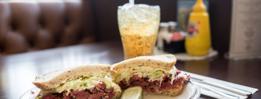 Langer's Number 19 sandwich with a pickle and a sparkling beverage