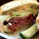 closeup off pastrami sandwich with a pickle