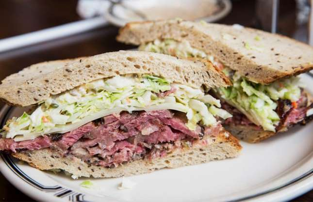 thick cut pastrami piled on a sandwich
