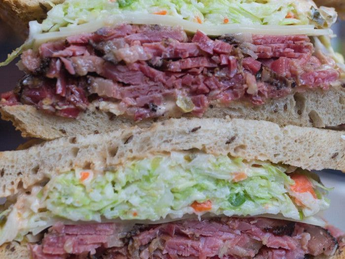 2 halves of a pastrami sandwich stacked on top of each other