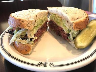 savory pastrami sandwich on rye bread with a pickle wedge on the side