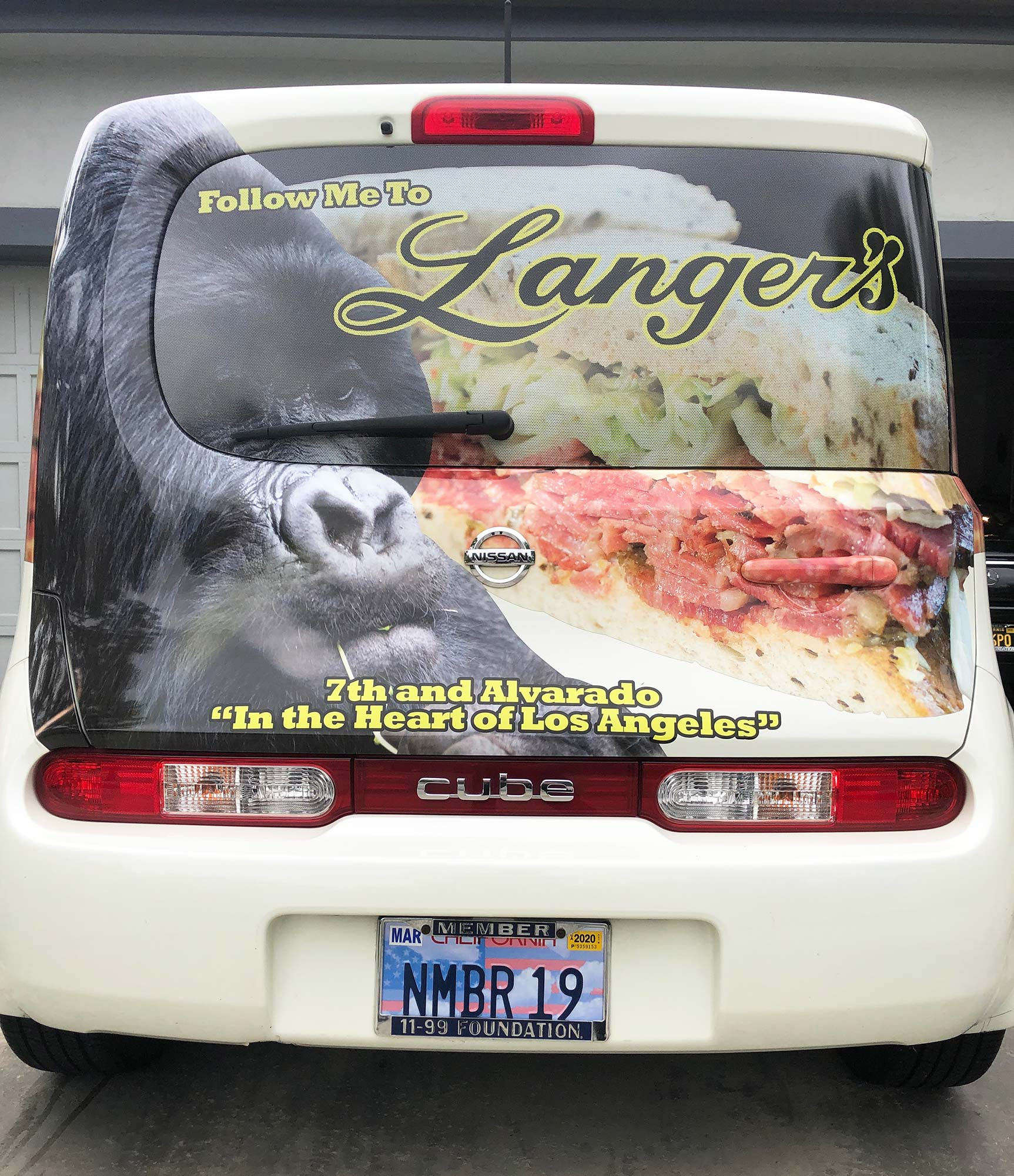 automobile covered in graphics reading follow me to Langer's