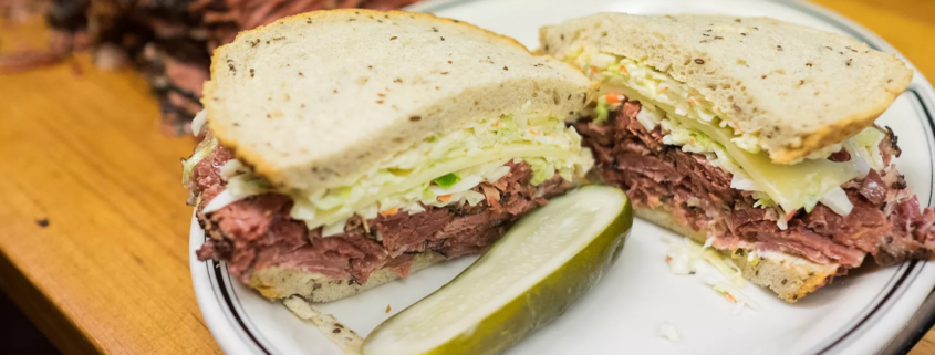 pastrami sandwich with swiss cheese and cole slaw on rye bread