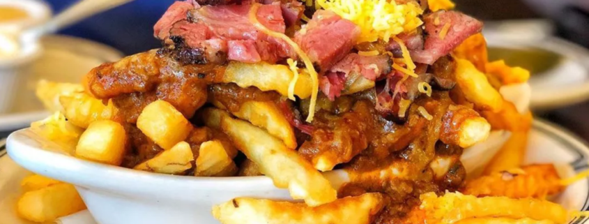 Pastrami on top of chili cheese fries piled high on a plate