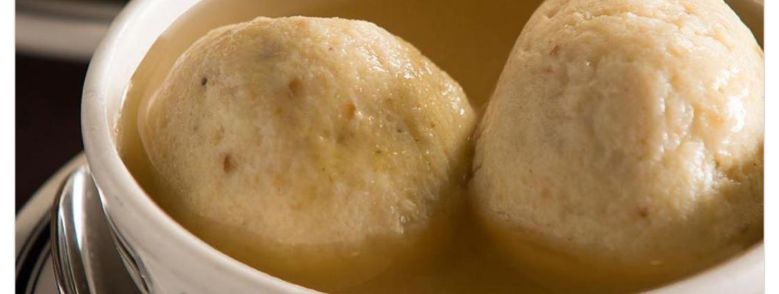 2 large dumplings floating in a bowl of broth