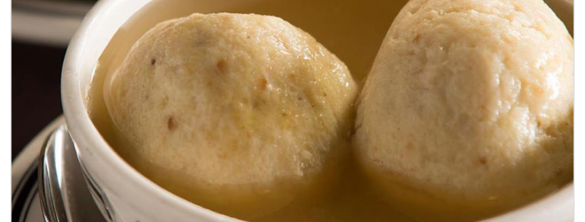 2 large dumplings floating in a bowl of broth