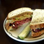 pastrami sandwich cut in half and garnished with a pickle