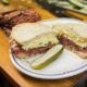 pastrami sandwich garnished with dill pickle