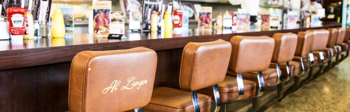 seats along the counter in a delicatessen