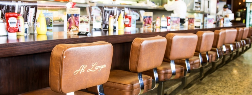 seats along the counter in a delicatessen